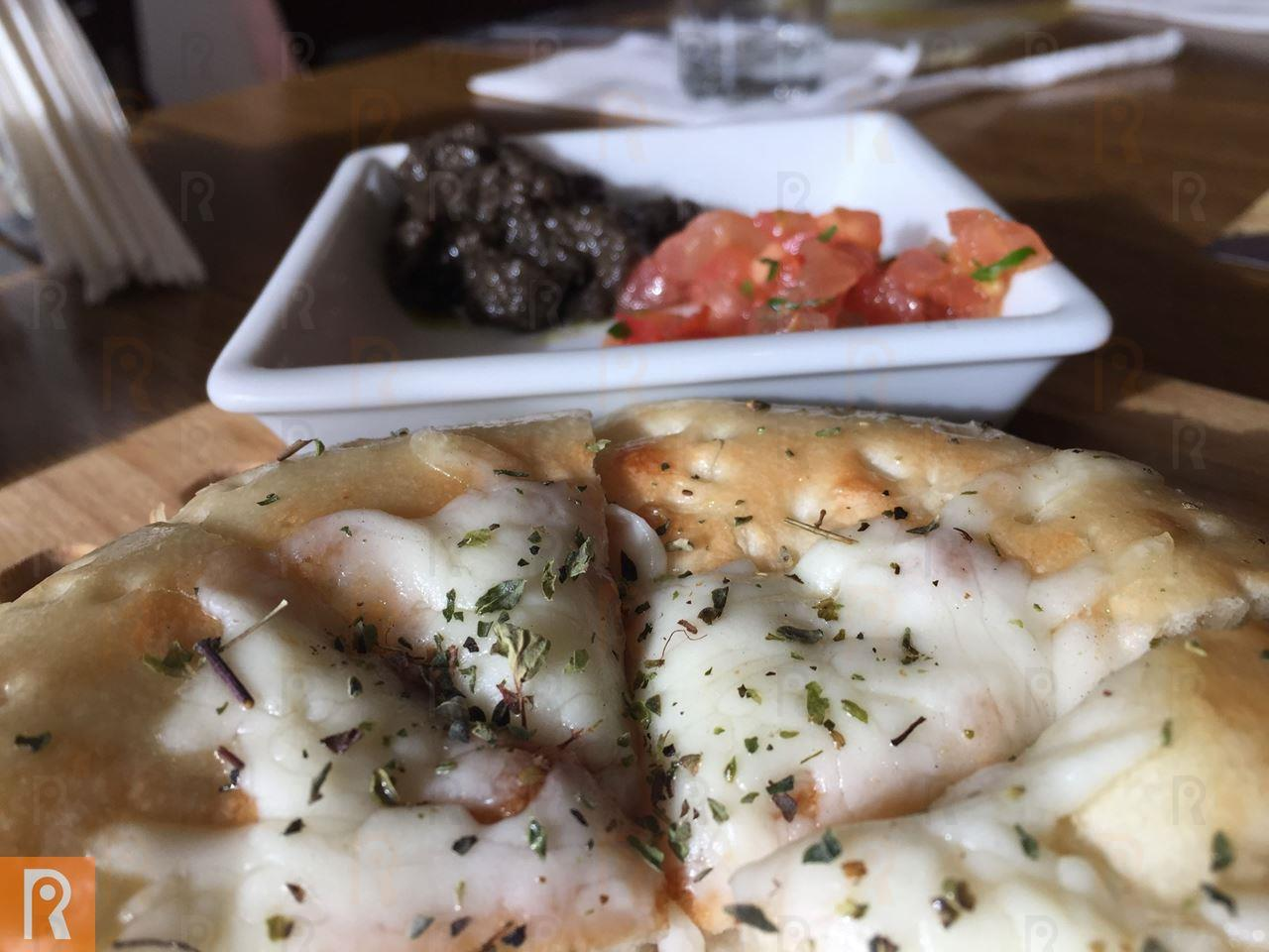 Bread with melted cheese along with tomatoes and olives